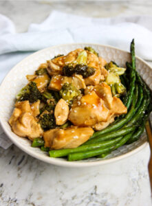 General Tso's Chicken served in white dish with rice and asparagus