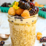 a jar of overnight oats topped high with toppings of fresh berries, cream and honey