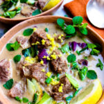 vertical photo of Low-FODMAP beef curry in rustic bowls with toppings of herbs and lemon