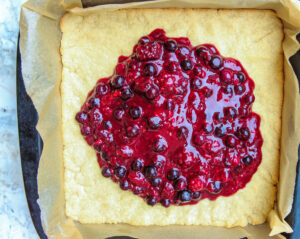 berry filling poured onto base after initial baking process photo