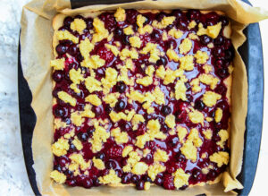 crumble topping crumbled over the berry filling before baking process photo