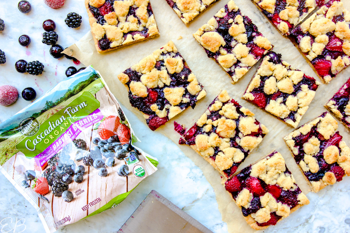 overhead view of berry crumble bars and bag of frozen berries