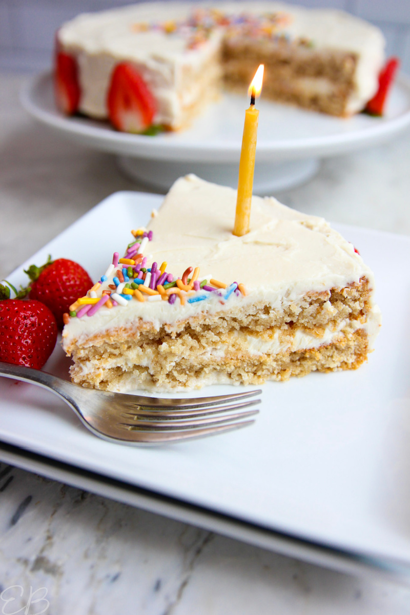 one slice on a plate with lit candle of aip birthday cake